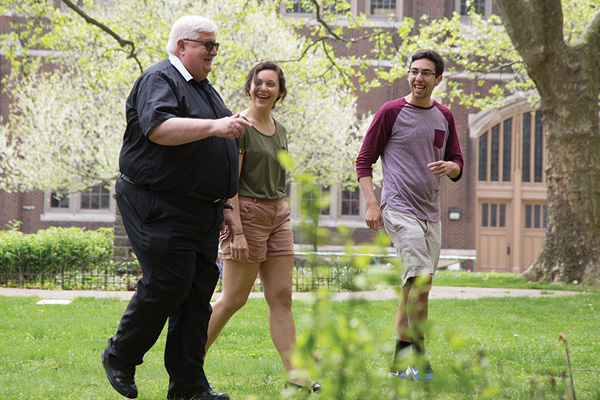 Students walking with Brother Bob on campus