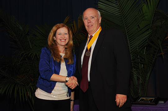 Dr. William J. Markmann, M.D., '70, receives the John J. Finley Award from AmyLynn Flood, '95, Vice President of the Alumni Association and Chair of the Awards Committee.