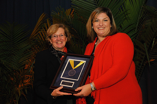 Christine DiBona Lobley, Executive Director of Fred's Footsteps (right) with the Signum Fidei Award, presented by Beth Harper Briglia (left). Between them is La Salle student Derek Marshall, whose family was helped by Fred's Foosteps.