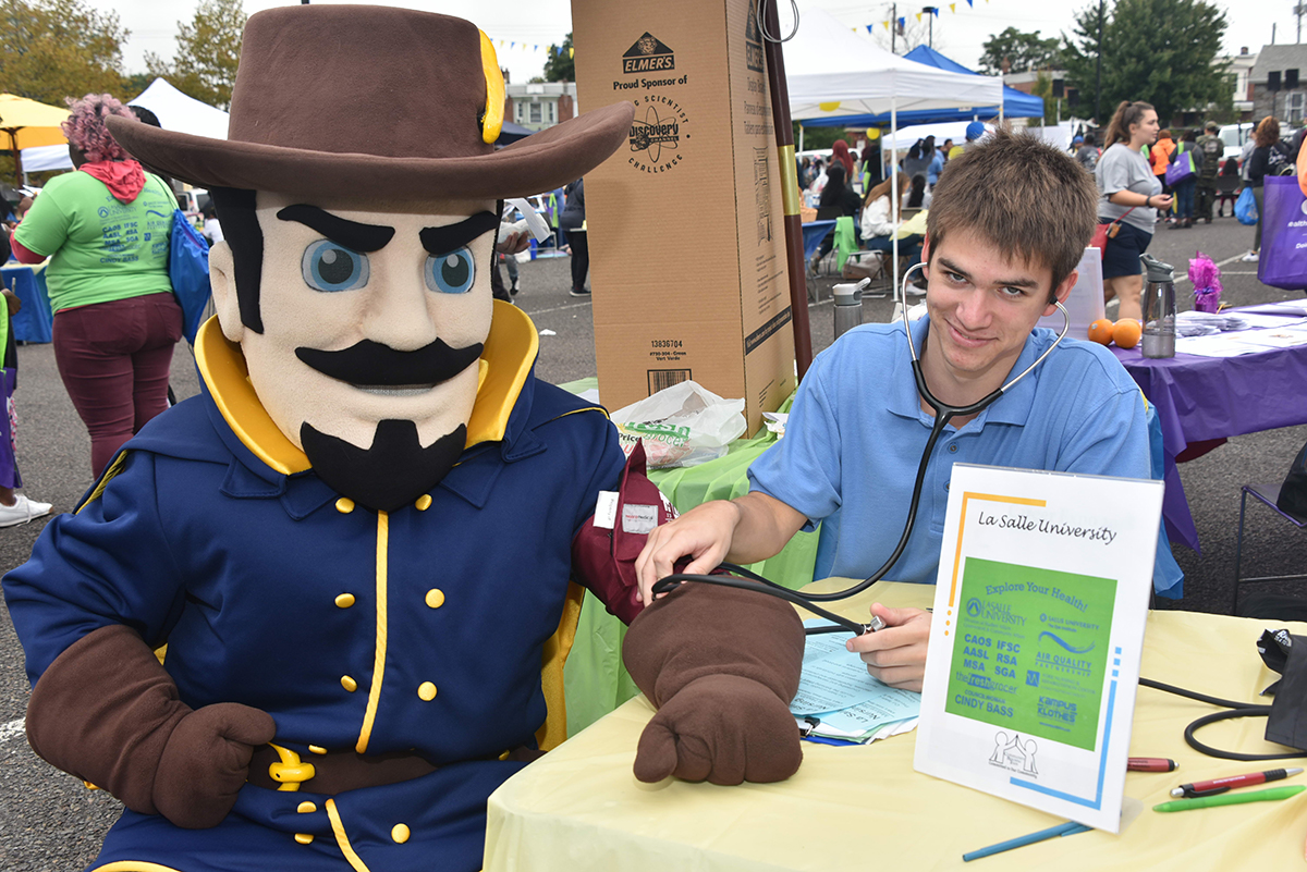 Student Nurse checking the Explorer Mascot's pulse.