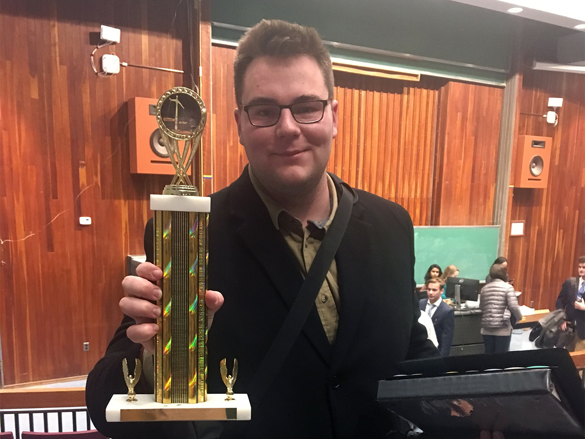 Jacob Garwood holds Trophy won by his mock trial team.