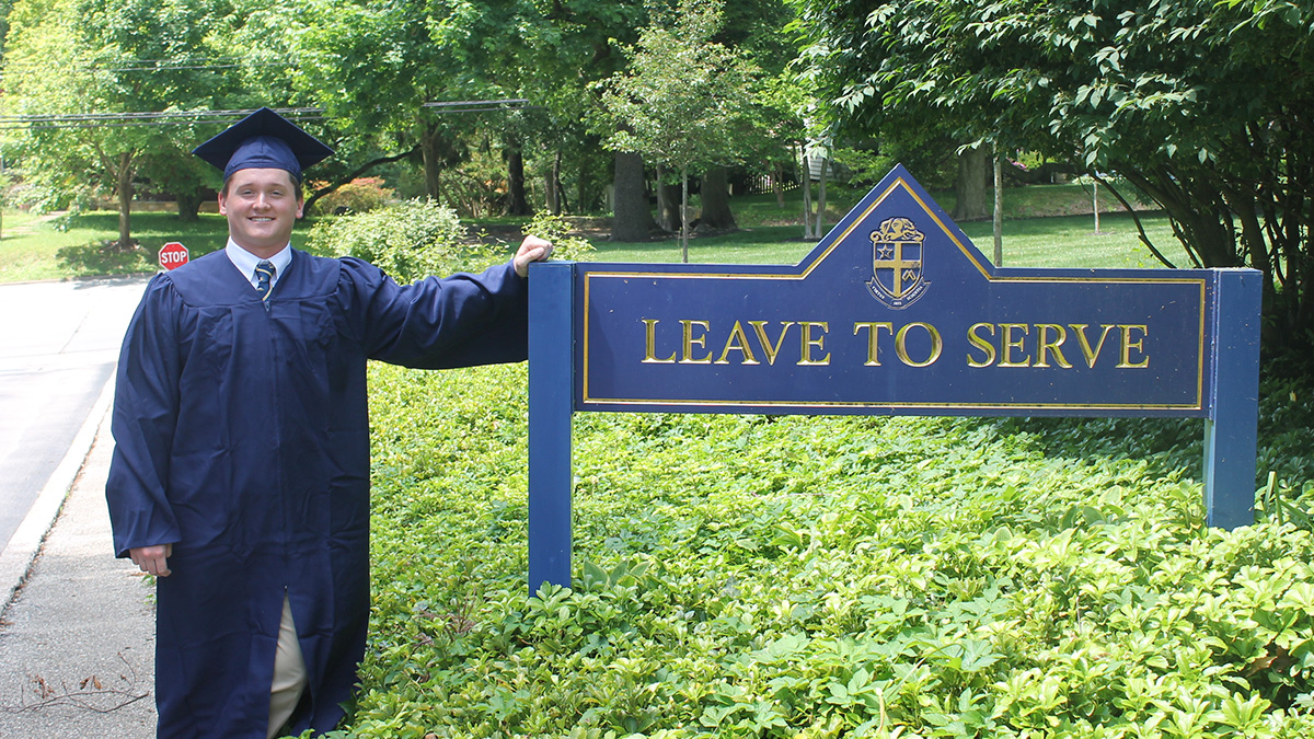 Liam McFadden in graduation gown next to signage