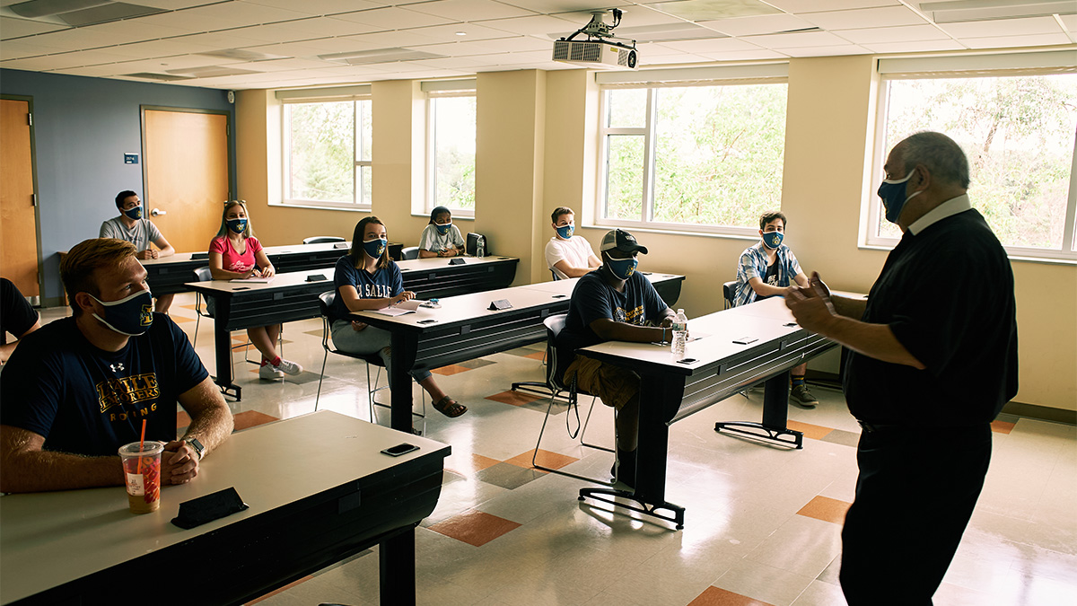 christian brother teaching classroom of students wearing masks