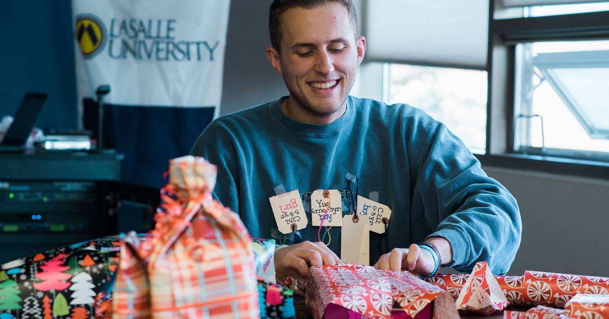 A student wraps a Christmas gift for the 2017 La Salle Toy Drive.