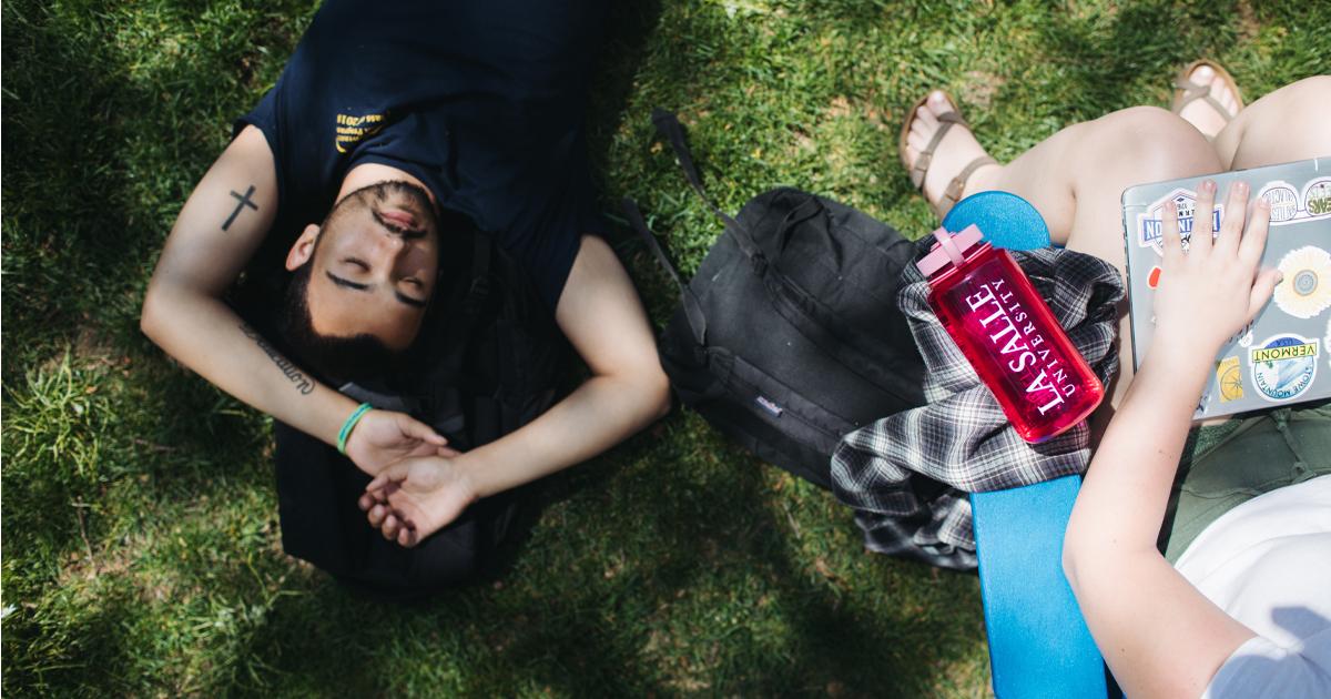 Image of student resting on the La Salle University quad