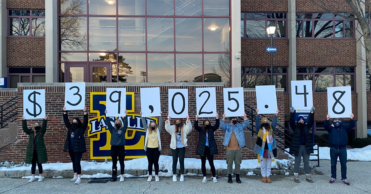 La Salle University students involved in Explorathon hold up signs indicating the amount of money they raised.