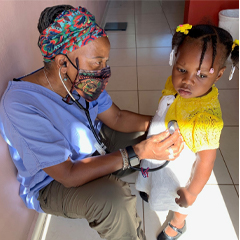 Image of Rhonda Hazell performing a wellness check on a young Haitian student.