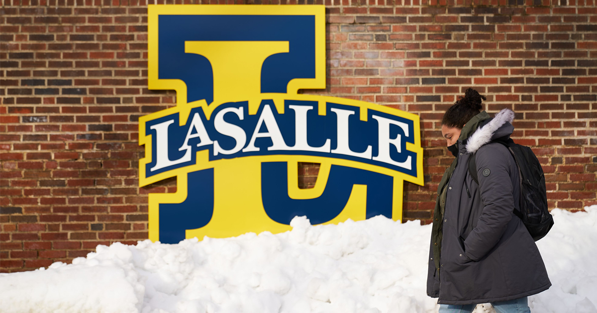 Image of a La Salle University student walking on campus after a snowstorm.