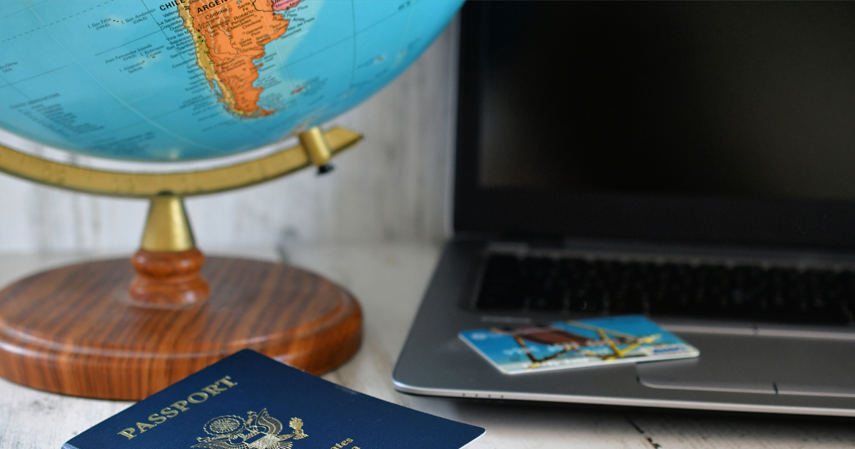 Image of a globe, laptop computer and passport.