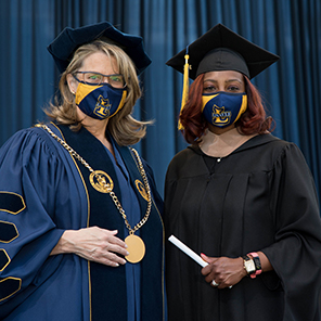 Image of La Salle University President Colleen Hanycz presenting a diploma to a graduating student at the University's commencement at Lincoln Financial Field in Philadelphia, May 15, 2021.