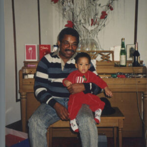 Image of Brandon Washington as a child sitting on his father Ron's lap.