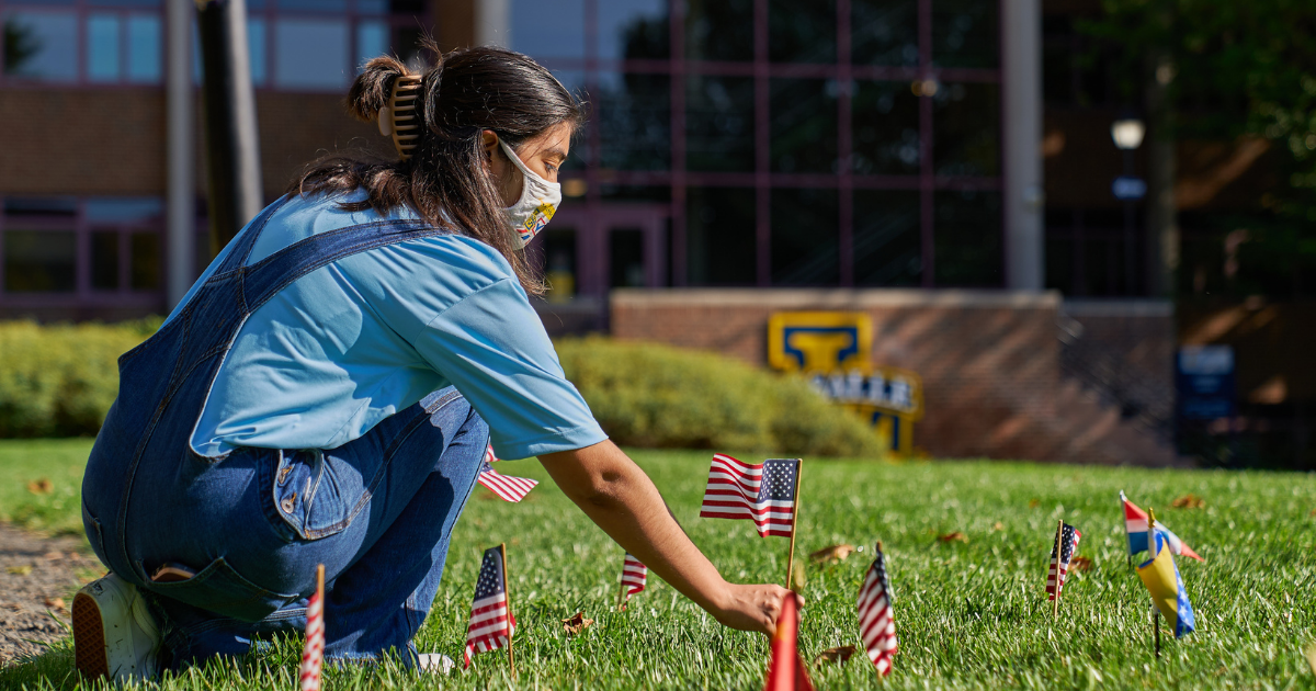A student putting flags into the ground on the Quad.