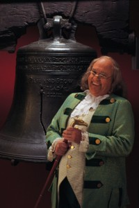 Man portraying Benjamin Franklin with liberty Bell