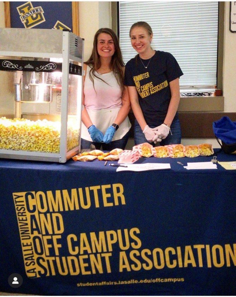 students at a booth representing COSA