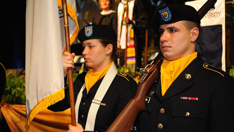 man and woman in military uniforms holding rifle and carrying flag