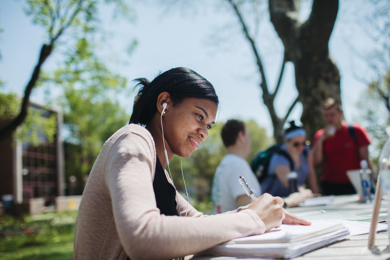 Female student working on classwork outdoors