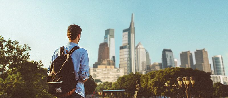 Male student standing in front of Philadelphia skyline in distance