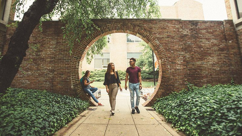male and female student walking together through an entranceway