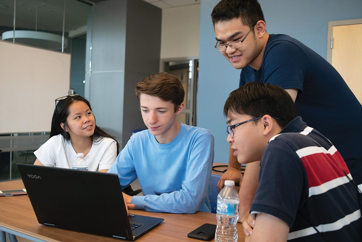 Summer Scholars students around a laptop
