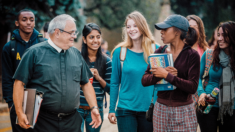 Brother Ed Sheehy walking with students