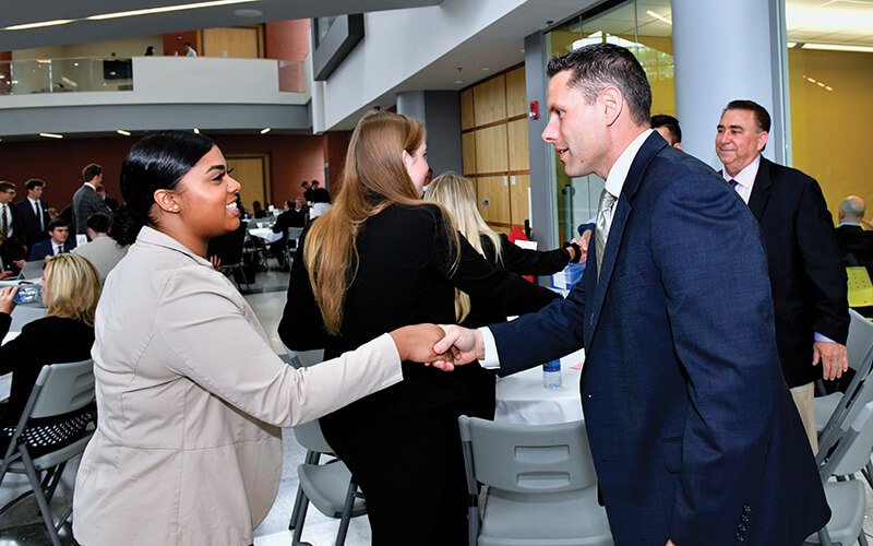 bankers day student shaking hands with mentor